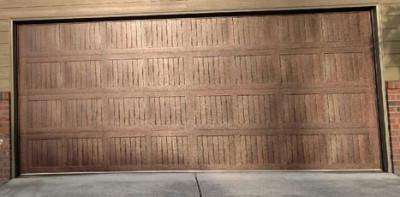 A metal garage door treated to resemble wood is seen.